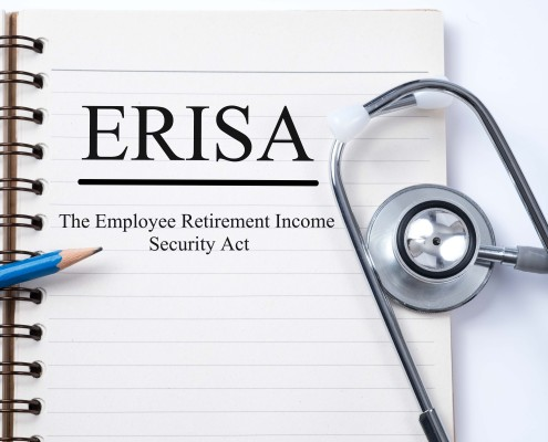 Stethoscope on notebook and pencil with ERISA (The Employee Retirement Income Security Act) words as medical concept.