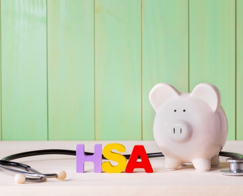 Health Savingins Account HSA concept with white  piggy bank, stethoscope wood block letters and green background